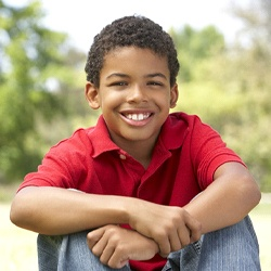 A young boy wearing a red shirt and sitting outside while smiling