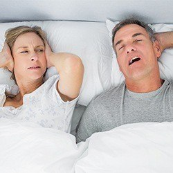 man snoring and wife covering ears