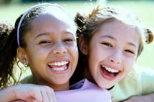 Two girls smiling after vising their family dentist