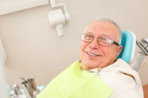 man smiling sitting in dental chair