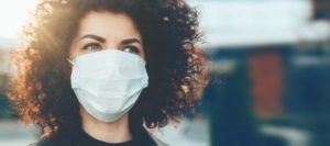 Woman in face mask going to see Waco dentist in COVID-19