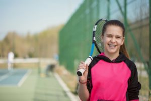 young girl with braces in Waco holding a tennis racket