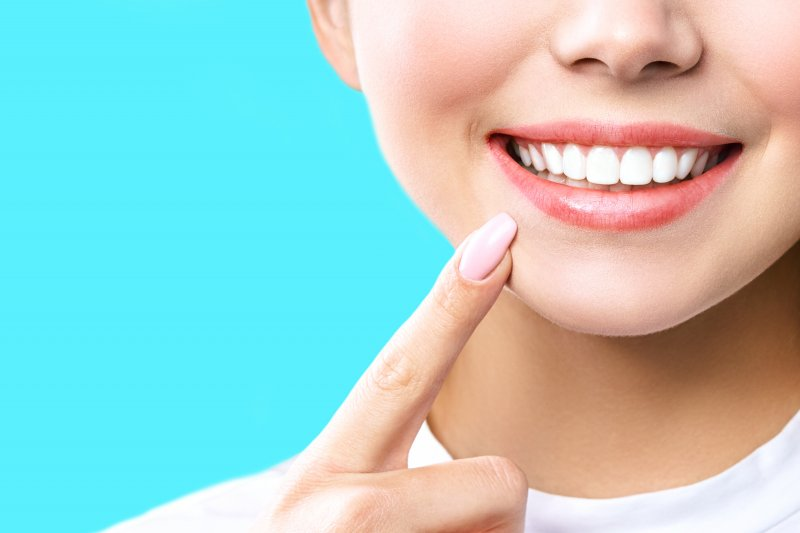 an up-close image of a person pointing to their whitened smile