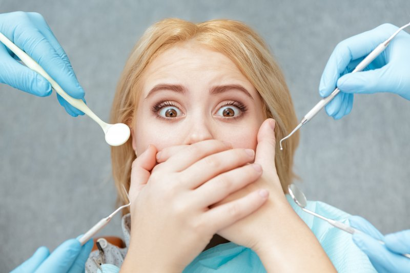 Scared woman protecting her mouth from dental tools