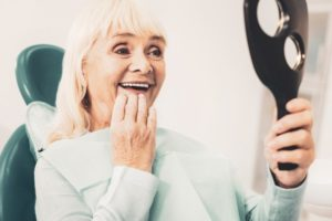 woman happy with implant-retained dentures in Waco
