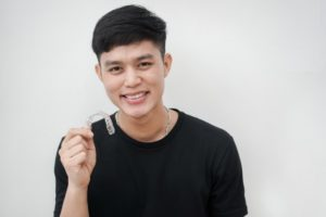 young man holding an aligner for Invisalign in Waco